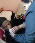 Helping a bedridden widow to drink a glass of milk