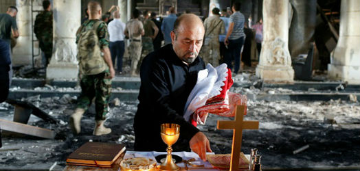 Priest sets the altar ready for service in a the war damaged church