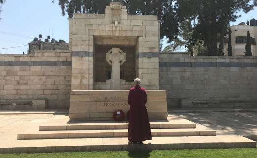 Archbishop Justin Welby standing facing the British war memorial at the Gaza War Cemetery