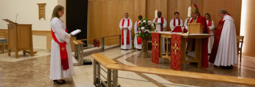 Revd Charlotte stands facing the bishop and clergy in front of the altar