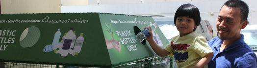 Little boy is lifted up to place bottle in recycling unit