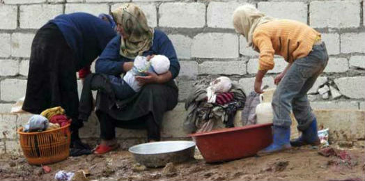 Two iraqi women and their children washing clothes in a tin bowl