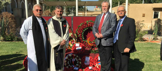 Archdeacon Bill Schwartz, Revd Faiz Jerges and John Banfields and Dawlat Abuna stand in front of the poppy wreaths