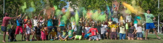 Young people in a group photo with colour dust bombs thrown over them