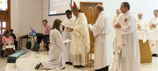 Charlotte Lloyd-Evans kneels in front of Bishop Michael during the service