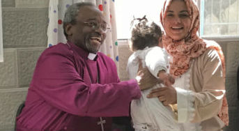Presiding Bishop Michael Curry hands a toddler back to her mother