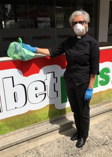 Rev Anne Futcher wearing mask and gloves delivering a food parcel
